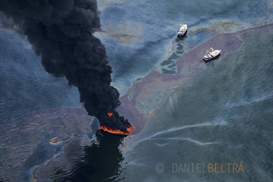 Two ships monitor a controlled burn from oil that was spilled from the wellhead. To aid in clean-up efforts, 5,300 vessels of opportunity were hired from around the area.